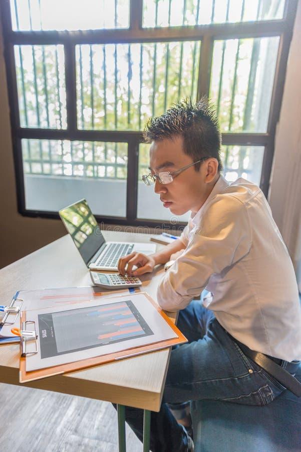 Młody Azjatycki księgowy pracuje na pieniężnych biznesowych dokumentach obraz stock
