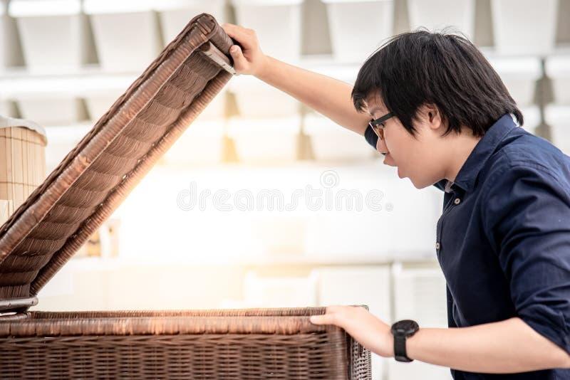 Młody Azjatycki mężczyzna otwiera drewnianego pudełko patrzeje inside zdjęcie stock