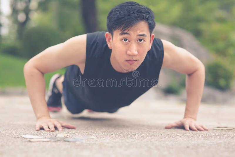Młody Azjatycki mężczyzna podnosi plenerowego robić pcha obraz royalty free