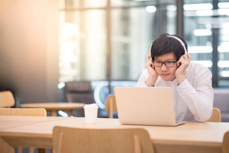 Młody Azjatycki mężczyzna słucha muzyka w workspace zdjęcie stock