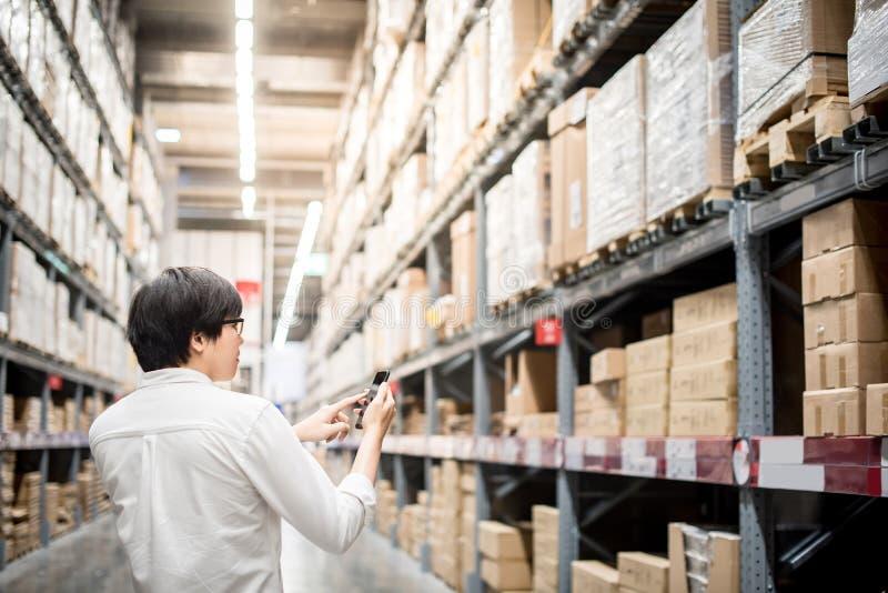Młody Azjatycki mężczyzna sprawdza listę zakupów od smartphone w wareho fotografia royalty free