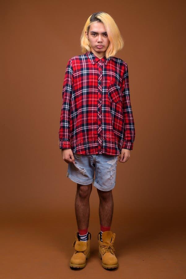 Młody Azjatycki mężczyzny być ubranym elegancki odziewa przeciw brązu tłu zdjęcie stock
