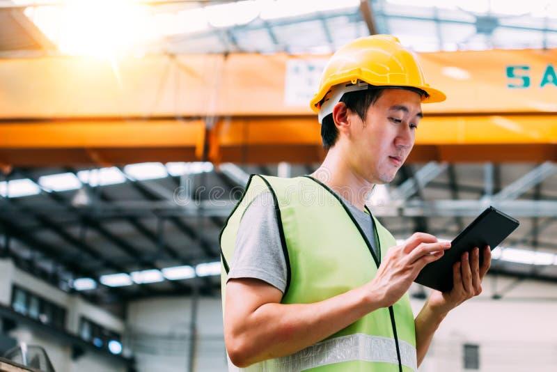 Młody Azjatycki męski pracownik fabryczny używa cyfrową pastylkę obraz royalty free