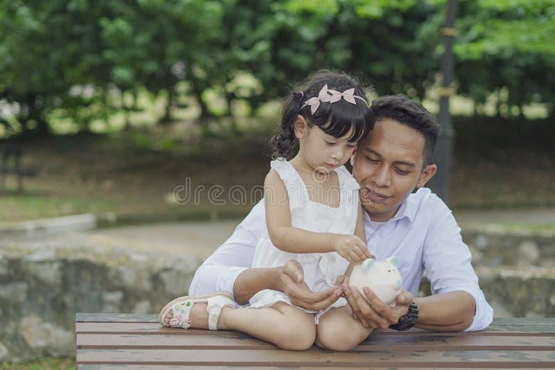 Młody Azjatycki ojciec uczy jego córki ratować pieniądze w prosiątko banka dla lepszy przyszłości fotografia stock