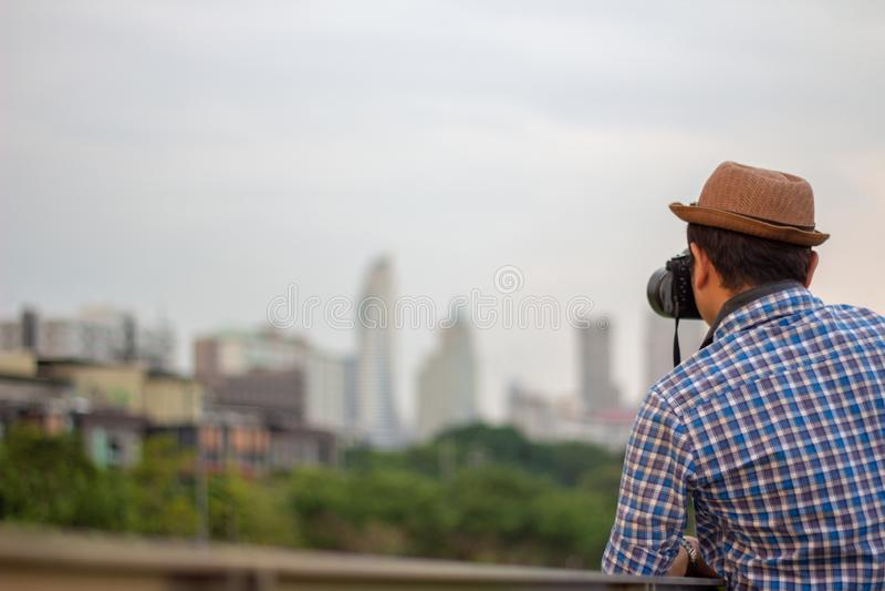 Młody Azjatycki podróżnika mężczyzna jest ubranym kapelusz bierze fotografię z dslr przychodził obraz stock