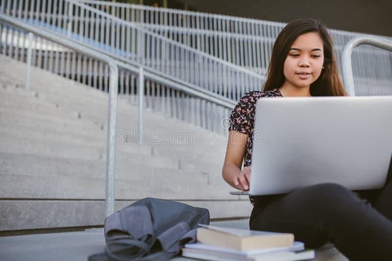 Młody Azjatycki student uniwersytetu używa laptop na kampusie zdjęcia stock