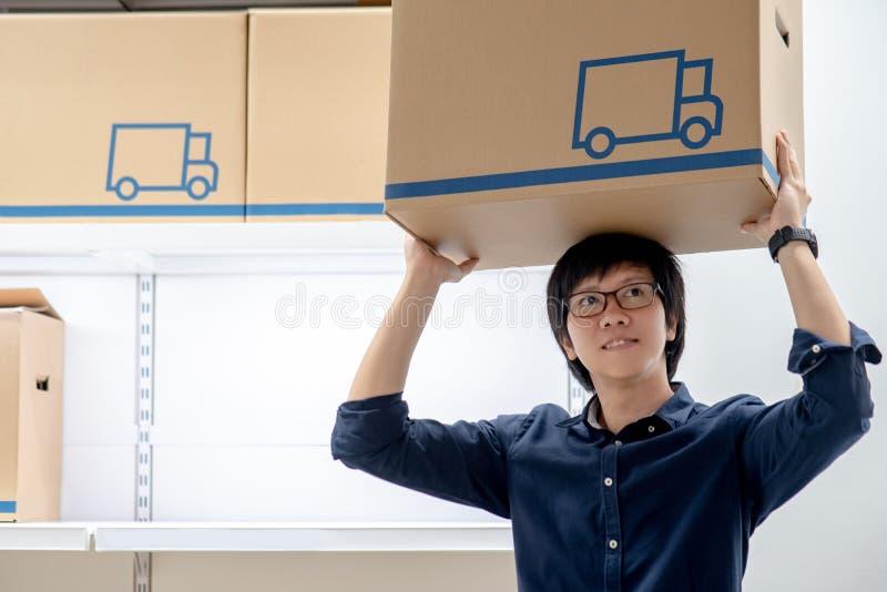 Młody Azjatycki szczęśliwy mężczyzna przewożenia kartonu koszt stały fotografia royalty free