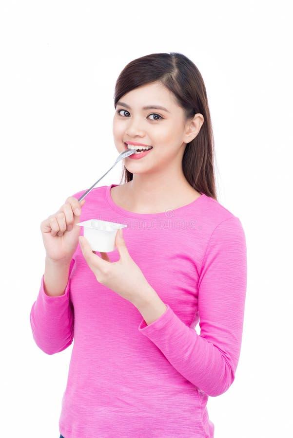 Młody azjatykci żeński cieszy się smak odizolowywający na bielu jogurt obraz stock
