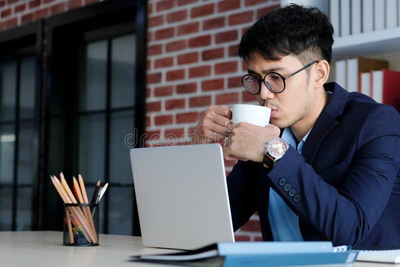 Młody azjatykci biznesmen pije kawę i działanie z laptopem przy biurem, biznesowego biura styl życia pojęcie zdjęcia royalty free