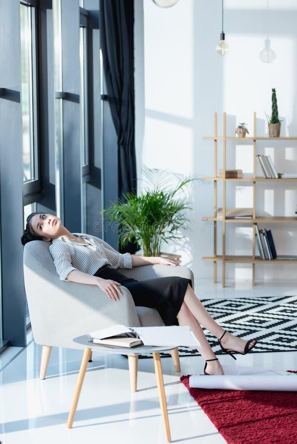 Młody azjatykci bizneswoman relaksuje podczas gdy siedzący na kanapie przy biurem fotografia stock