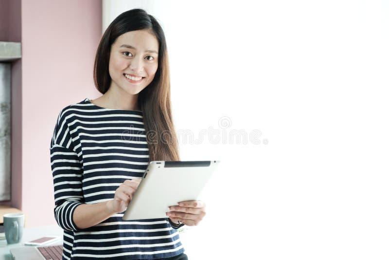 Młody azjatykci bizneswoman używa pastylkę z uśmiechniętą twarzą, positi zdjęcia stock