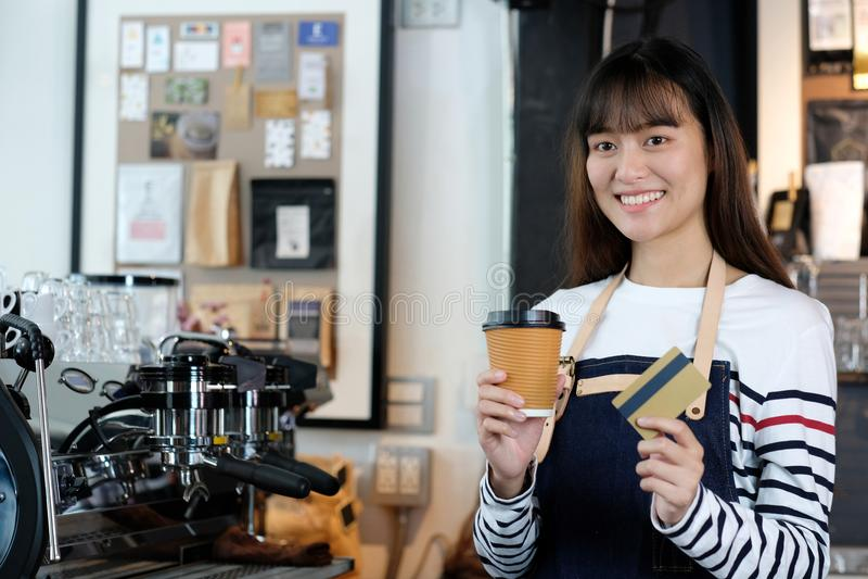 Młody azjatykci kobiety barista trzyma rozporządzalnego cr i filiżankę fotografia royalty free