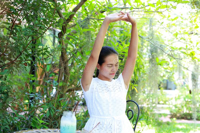 Młody azjatykci kobiety obsiadanie i relaksuje przy plenerową kawiarnią zdjęcia royalty free