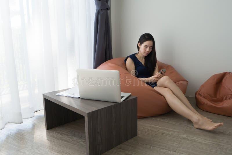 Młody azjatykci kobiety obsiadanie na bobowej torbie i używać mądrze telefon, pastylka, telefon komórkowy z plecy ekranu laptopem obrazy royalty free