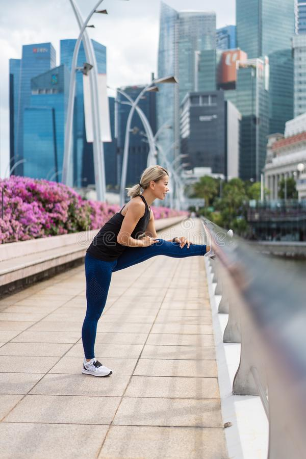 Młody azjatykci kobiety robić niektóre grże w górę ćwiczeń i rozciągać przed biegać na mieście fotografia stock