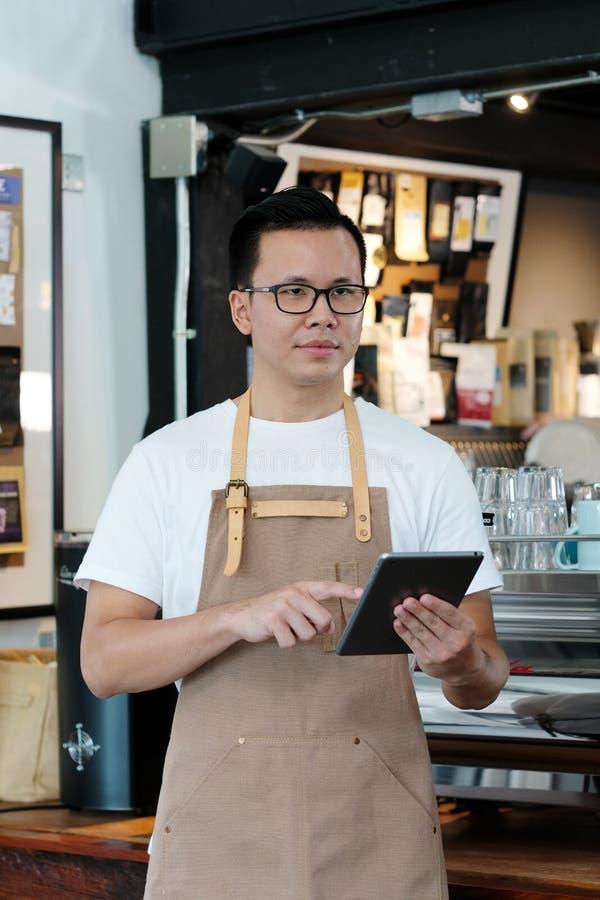 Młody azjatykci mężczyzna, barista, używać pastylkę przy kawiarnia kontuaru backgroun zdjęcia stock