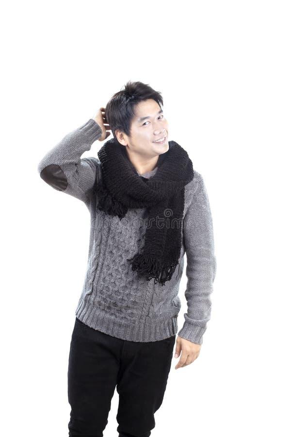 Młody azjatykci mężczyzna jest ubranym przędza pulower dziającego z czarną wełna szalika pozycją z szczęśliwą twarzą odizolowywał zdjęcia royalty free