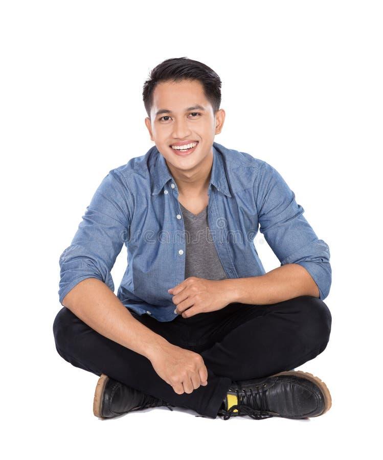 Młody azjatykci mężczyzna obsiadanie na podłoga, uśmiech zdjęcia royalty free