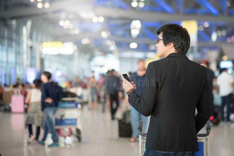 Młody azjatykci mężczyzna używa smartphone w lotniskowym terminal zdjęcia royalty free