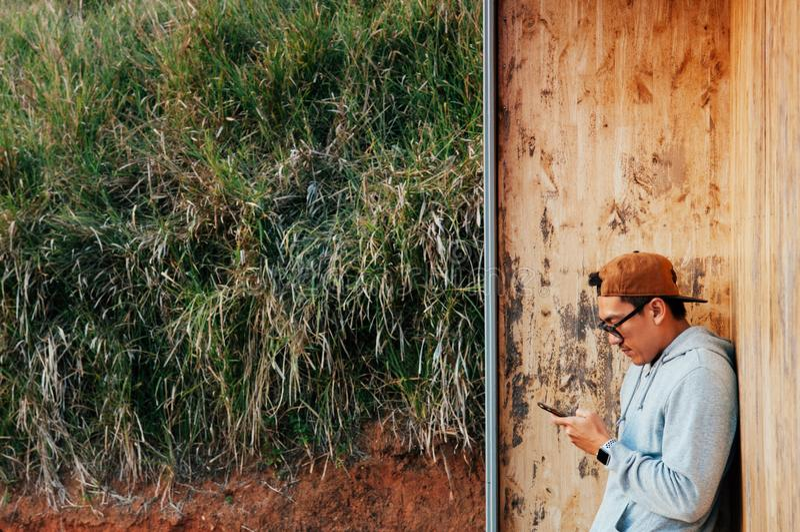 Młody azjatykci mężczyzna używa telefonu komórkowego stojaka przeciw drewnianemu ściennemu dowcipowi zdjęcia royalty free