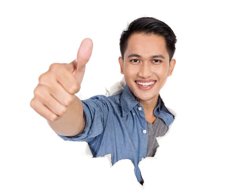Młody azjatykci mężczyzna w rozdzierającym papierowym i pokazuje kciuku up zdjęcia royalty free
