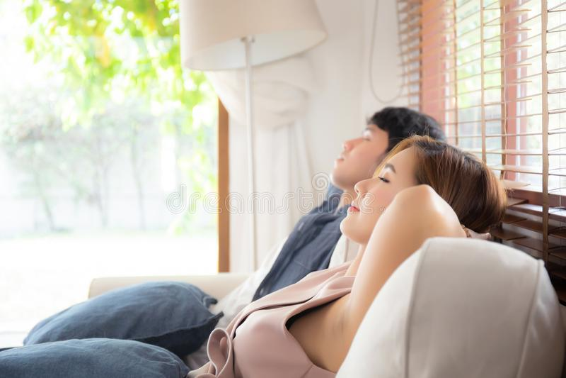 Młody azjatykci para uśmiech relaksuje wygodnego na kanapie w żywym pokoju w wakacje, rodzinnym czasie wolnym i odpoczywać z szcz obrazy stock