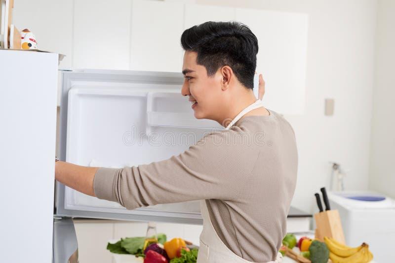 Młody azjatykci przystojny mężczyzna narządzania jedzenie w kuchni w domu obraz stock