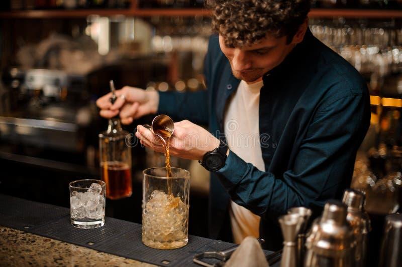 Młody barman nalewa słodkiemu syropowi w słój z lodowym robić alkoholicznego napój zdjęcia stock