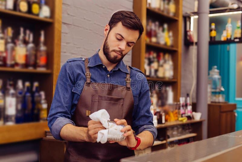 Młody barman patrzeje koncentrujący podczas gdy czyścić szkła obraz stock