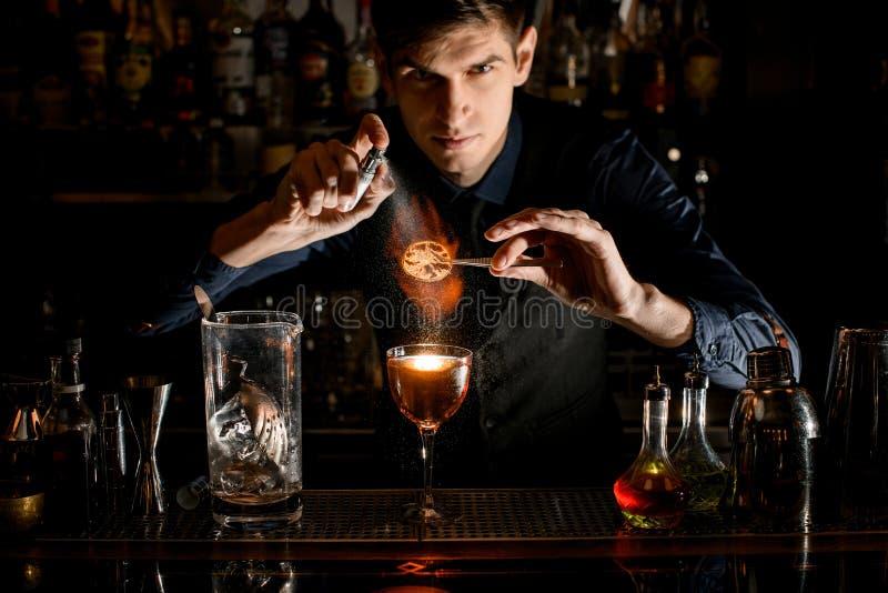 Młody barman profesjonalnie trzyma pęsety z kawałkiem cytrusów nad szklanymi posypkami i podpala je. fotografia royalty free