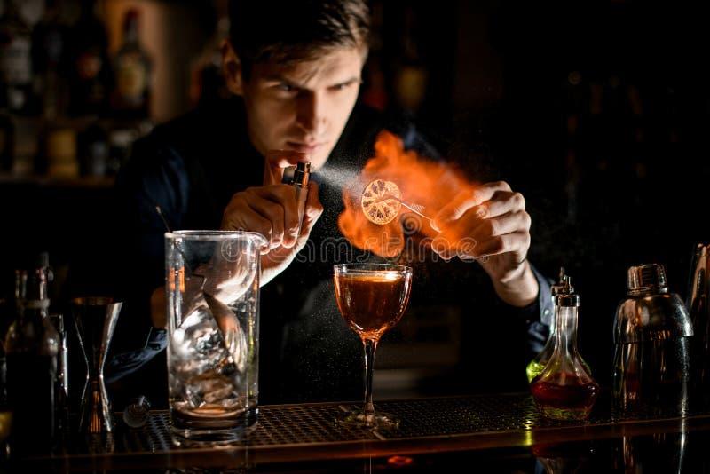 Młody barman trzyma pęsety z kawałkiem cytrusów nad szklanymi posypkami i podpala je. obraz stock