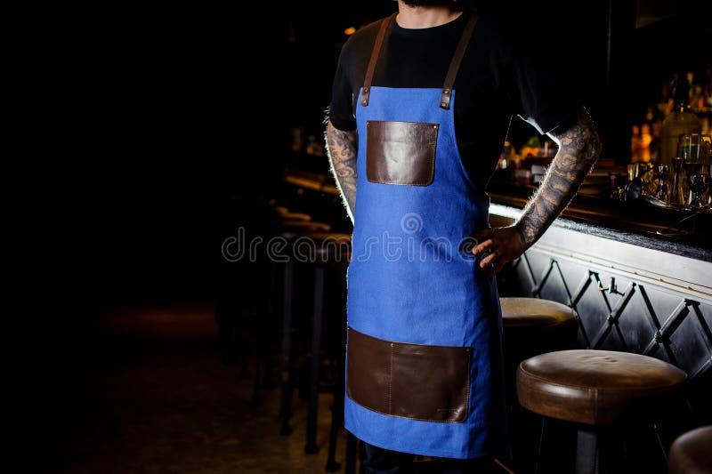 Młody barman z tatuażem na rękach ubierał w błękitnym i brown fartuchu obraz stock