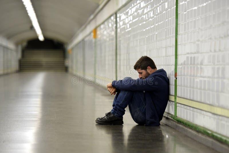 Młody bezdomny mężczyzna gubjący w depresji obsiadaniu na zmielonym ulicznym metro tunelu zdjęcie royalty free