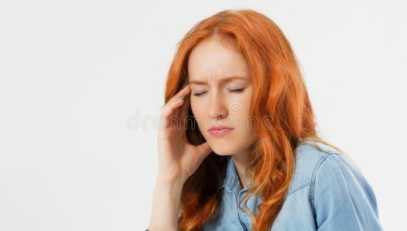 Młody beznadziejny czerwony włosiany kobiety cierpienie od depresji ma załamanie nerwowe trzyma jej głowę na odosobnionym tl obraz royalty free