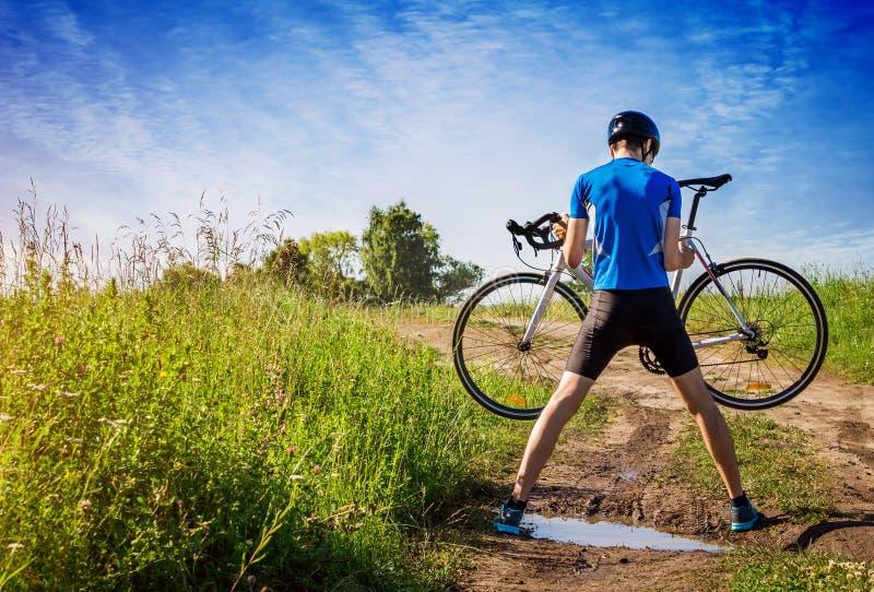 Młody bicyclist niesie jego rower przez kałużę fotografia royalty free