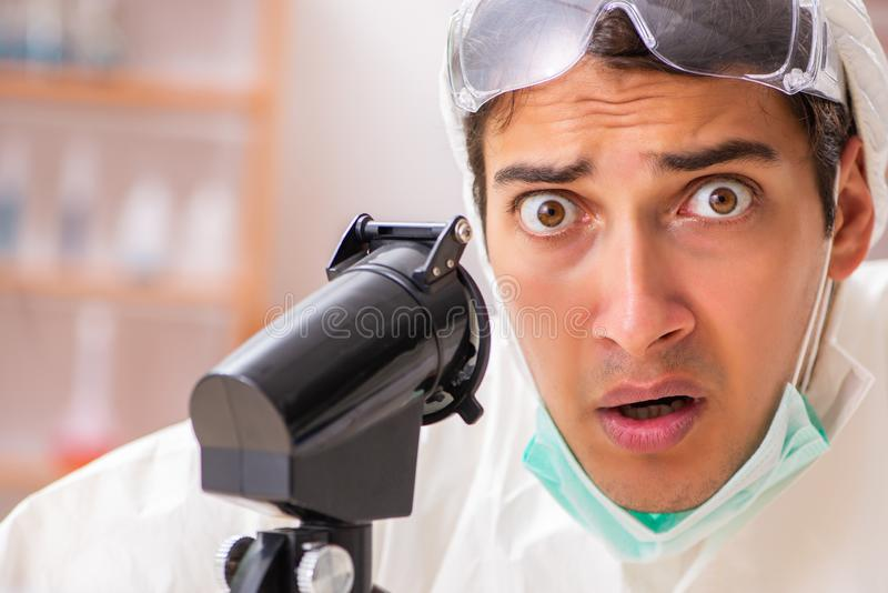 Młody biochemik jest ubranym ochronnego kostium pracuje w lab zdjęcia royalty free