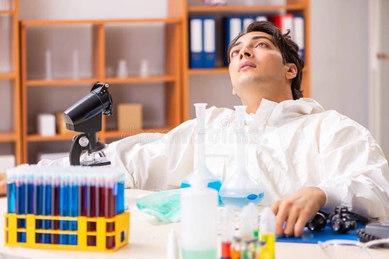 Młody biochemik jest ubranym ochronnego kostium pracuje w lab fotografia royalty free