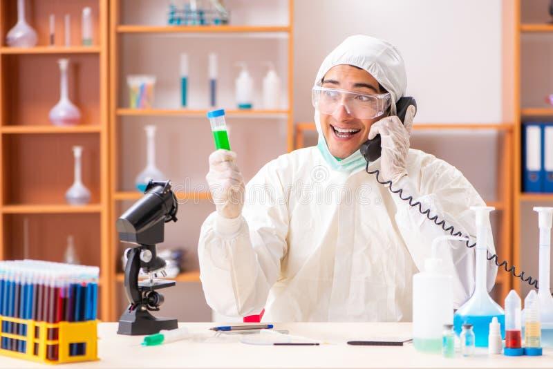 Młody biochemik jest ubranym ochronnego kostium pracuje w lab obrazy stock