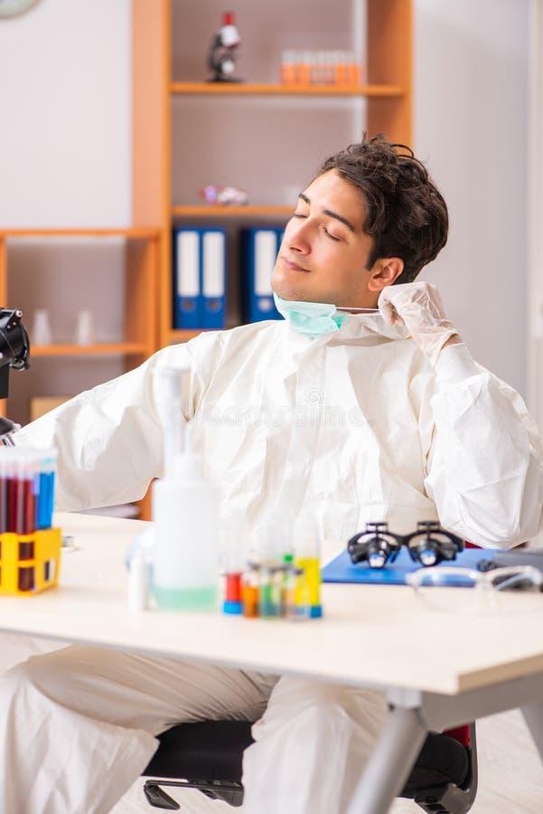 Młody biochemik jest ubranym ochronnego kostium pracuje w lab zdjęcia stock