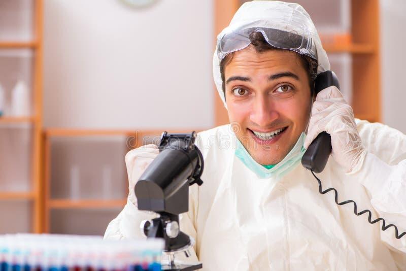Młody biochemik jest ubranym ochronnego kostium pracuje w lab fotografia stock