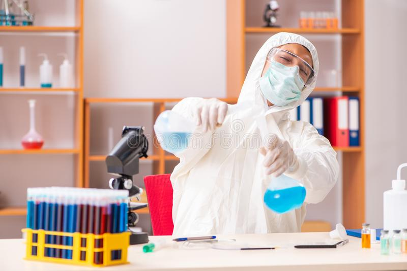 Młody biochemik jest ubranym ochronnego kostium pracuje w lab obrazy royalty free
