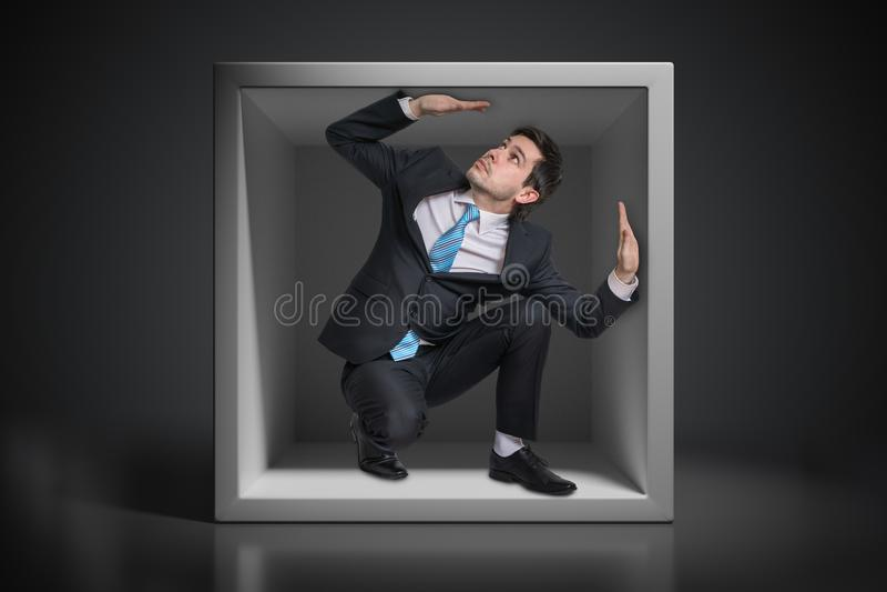 Młody biznesmen łapać w pułapkę inside niewygodny mały pudełko zdjęcie stock