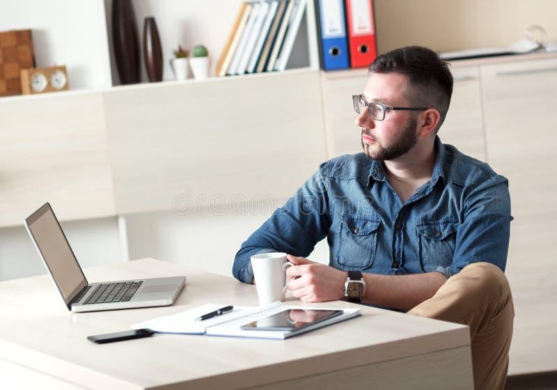 Młody biznesmen bierze kawową przerwę w jego biurze zdjęcia stock