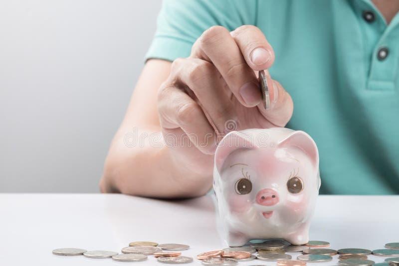 Młody biznesmen deponuje pieniądze w prosiątko banku zdjęcie royalty free