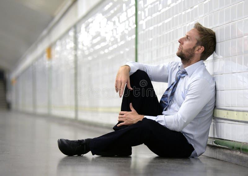 Młody biznesmen gubjący w depresji obsiadaniu na zmielonym ulicznym metrze zdjęcie stock