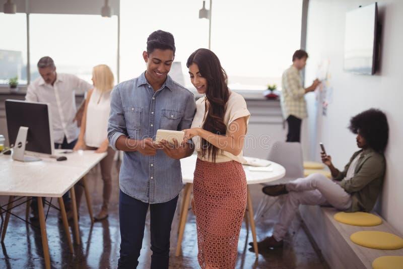 Młody biznesmen i bizneswoman dyskutuje nad cyfrową pastylką z kolegami w tle obrazy stock