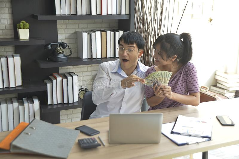 Młody biznesmen i bizneswomany trzyma pieniądze zysk zdjęcia stock