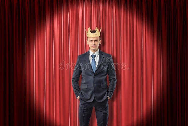 Młody biznesmen jest ubranym złotą koronę na czerwonym scen zasłoien tle fotografia stock