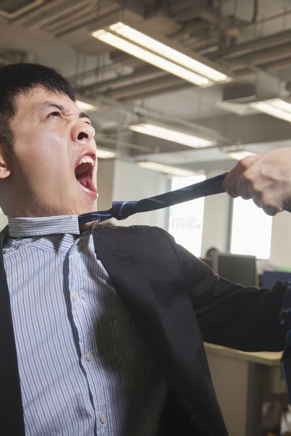 Młody biznesmen ma jego krawat ciągnął wewnątrz biuro zdjęcie stock
