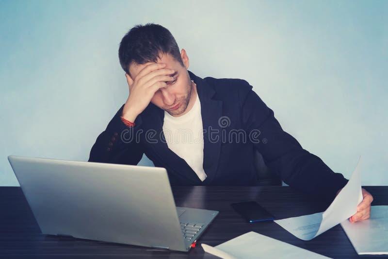 Młody biznesmen marszczy brwi przy jego ekranem komputerowym z problemem przy biurowym obsiadaniem przy jego biurkiem z jego ręka fotografia royalty free
